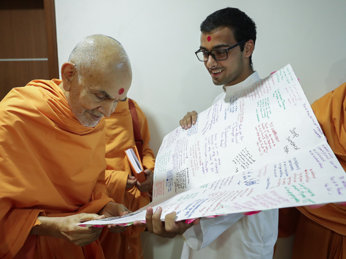 Swamishri reads messages on a card prepared by youths
