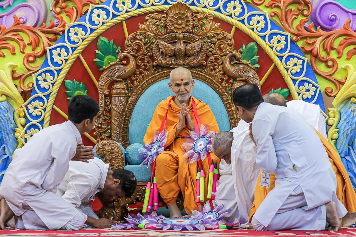 Vidyamandir representatives honor Swamishri with a garland