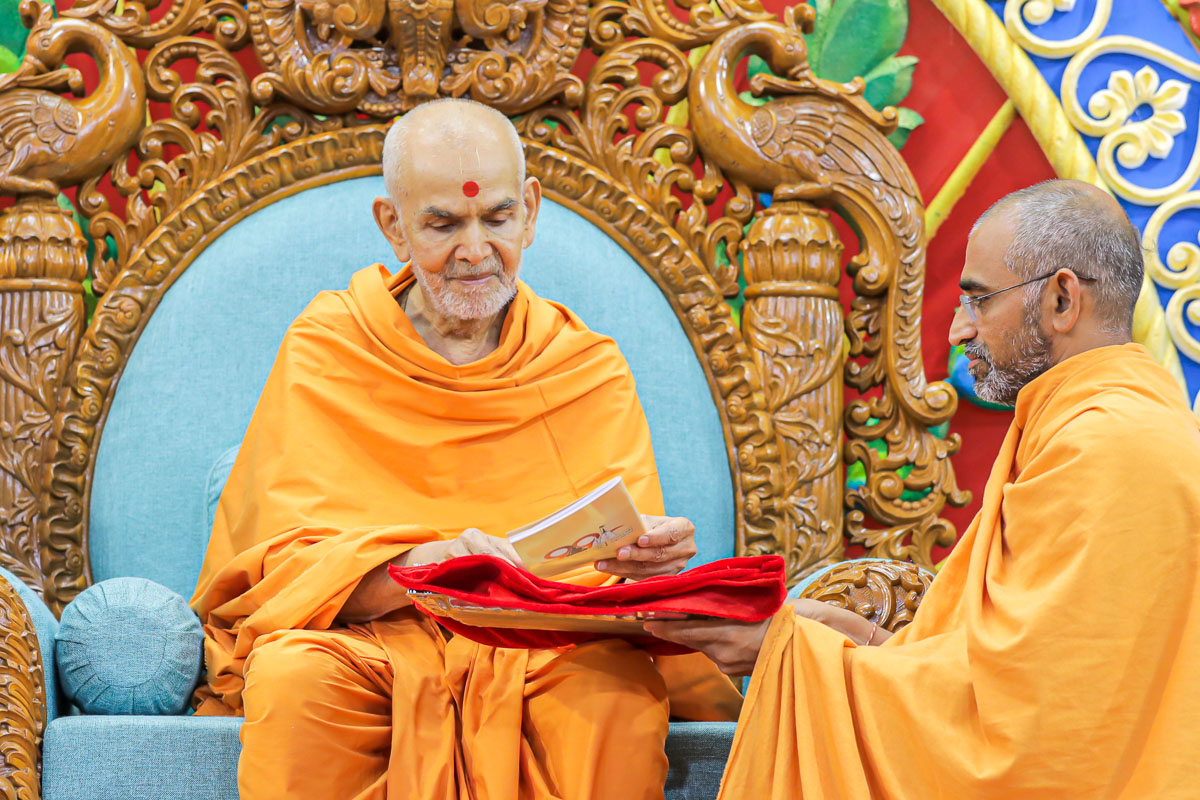 Swamishri sanctifies a book for the Vidyamandir