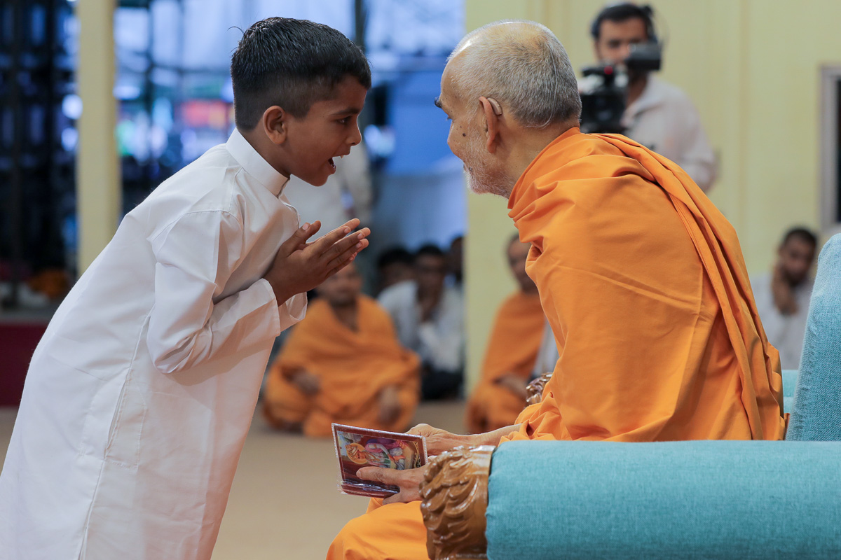 Swamishri converses with a child