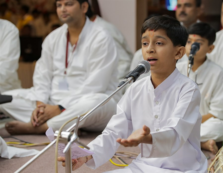 A child sings a kirtan in Swamishri's daily puja
