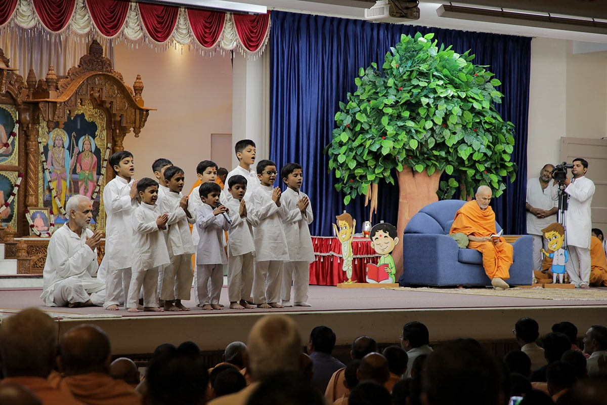 Children lead everyone in reciting the sadhana mantra and daily prayer in Swamishri's puja