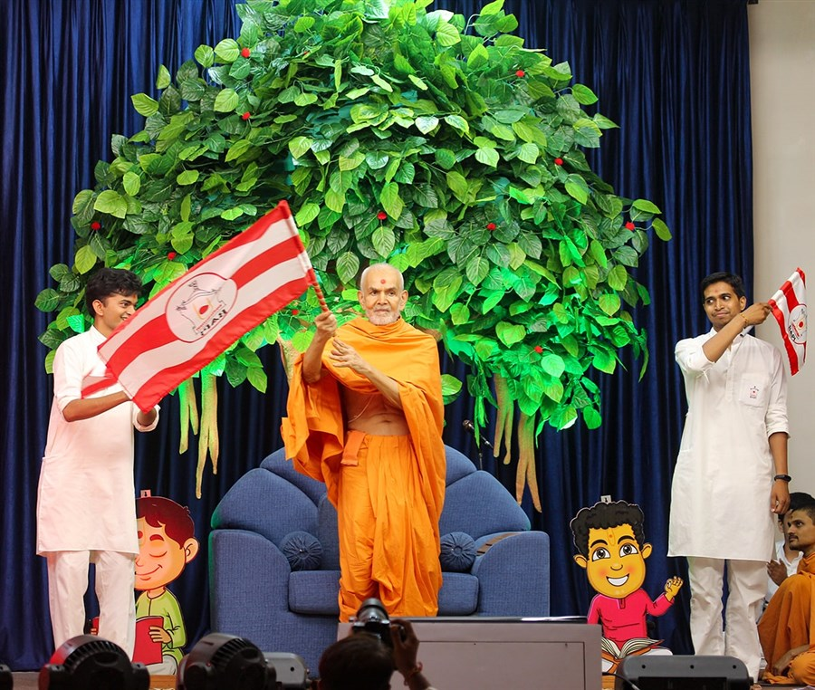 Swamishri and karyakars wave BAPS flags