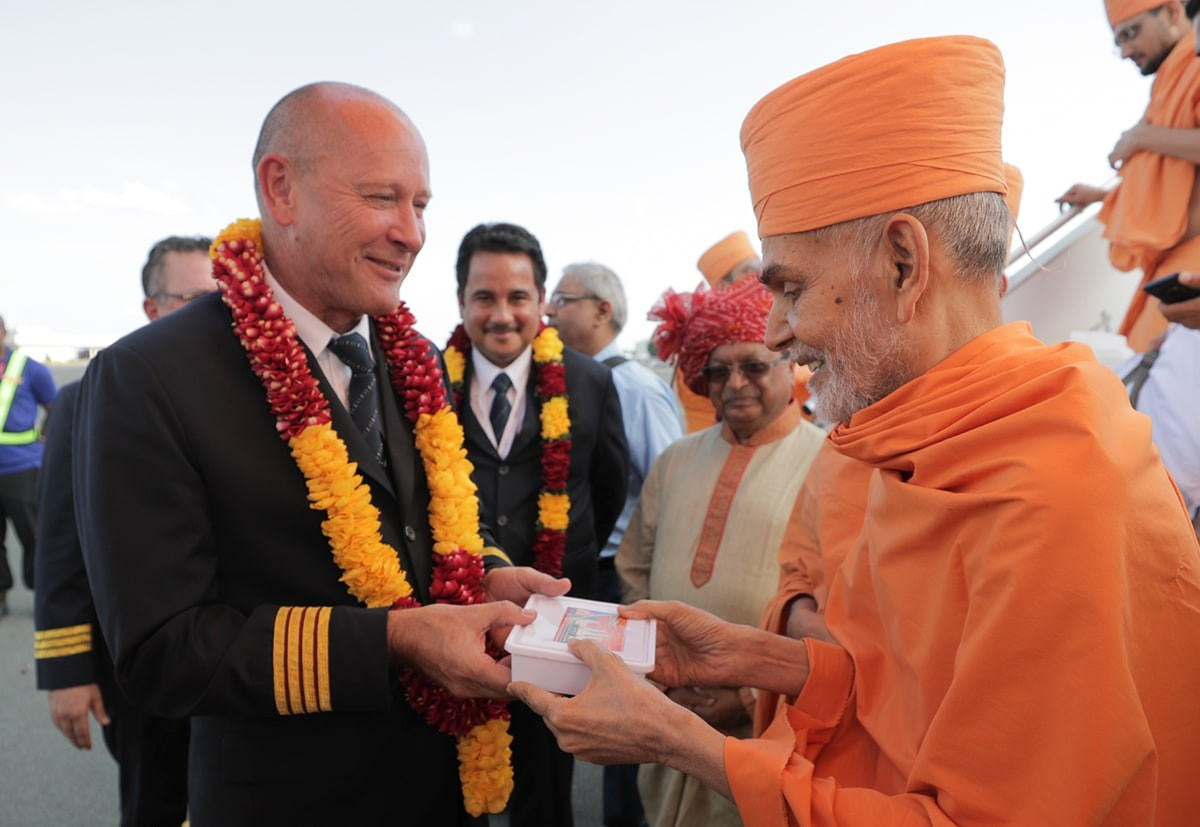 Swamishri gives prasad to the captain