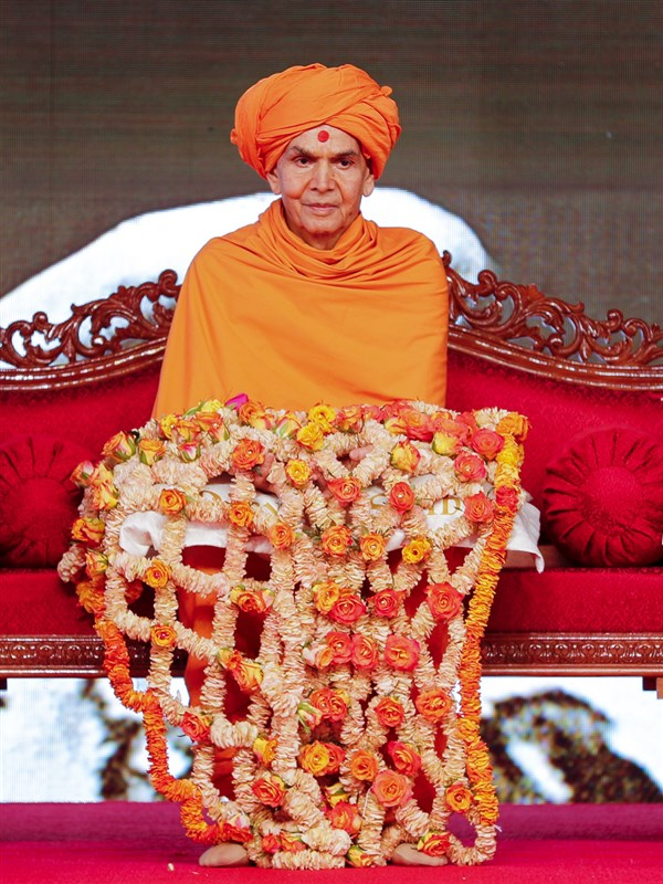 Swamishri honored with a shawl of flowers
