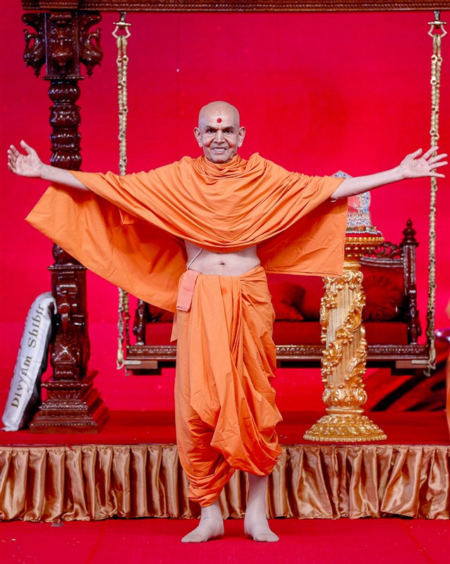 Swamishri gestures to embrace all
