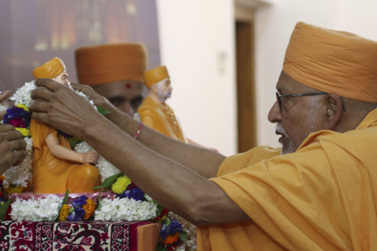 Pujya Kothari Swami honors murtis with a garland