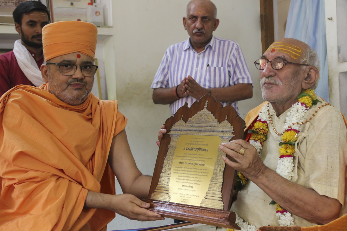 Pujya Bhadresh Swami felicitates Pandit Ramyatna Shukla (president of Kashi Vidvat Parishad) on behalf of the BAPS
