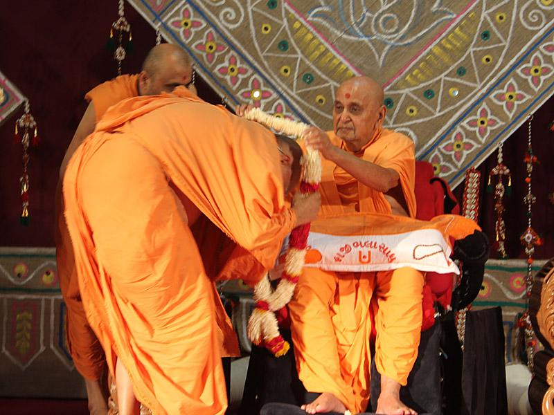 After honoring Swamishri with a garland Swamishri garlands Ishwarcharan Swami