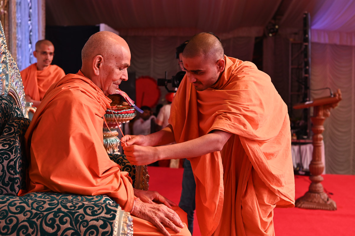 Paramkirti Swami presents an ID card to Swamishri
