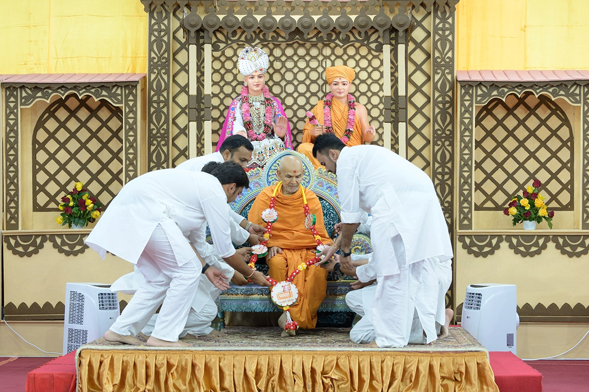 Youths honor Swamishri with a garland