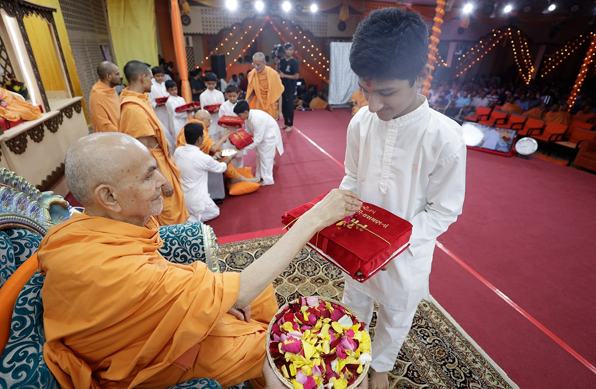 Swamishri showers flower petals on a Vachanamrut