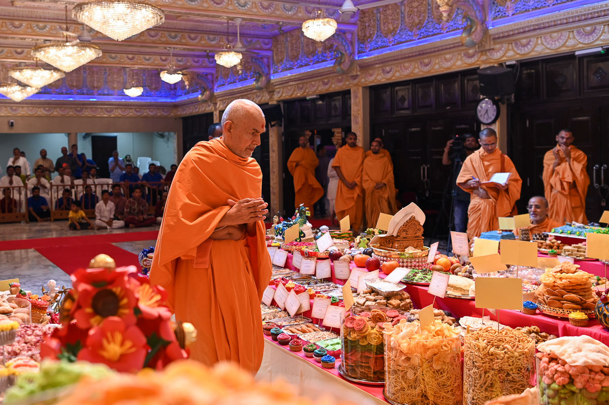 Swamishri engrossed in darshan of the annakut offered to Thakorji