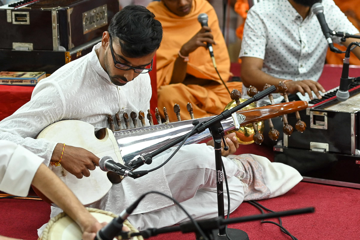 A youth plays sarod in Swamishri's daily puja