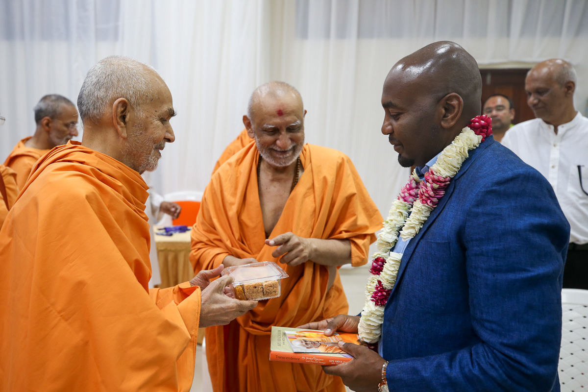 Swamishri gives prasad to Mr. Hamad Masauni, Deputy Home Minister of Tanzania