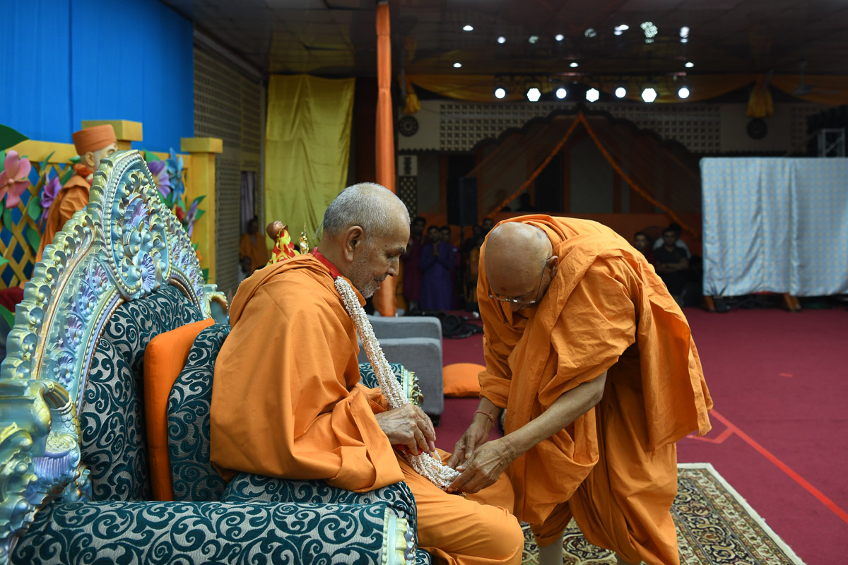 Pujya Tyagvallabh Swami honors Swamishri with a garland