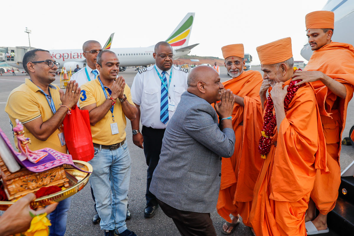 Devotees welcome Param Pujya Mahant Swami Maharaj with a garland at the Entebbe airport, Uganda
