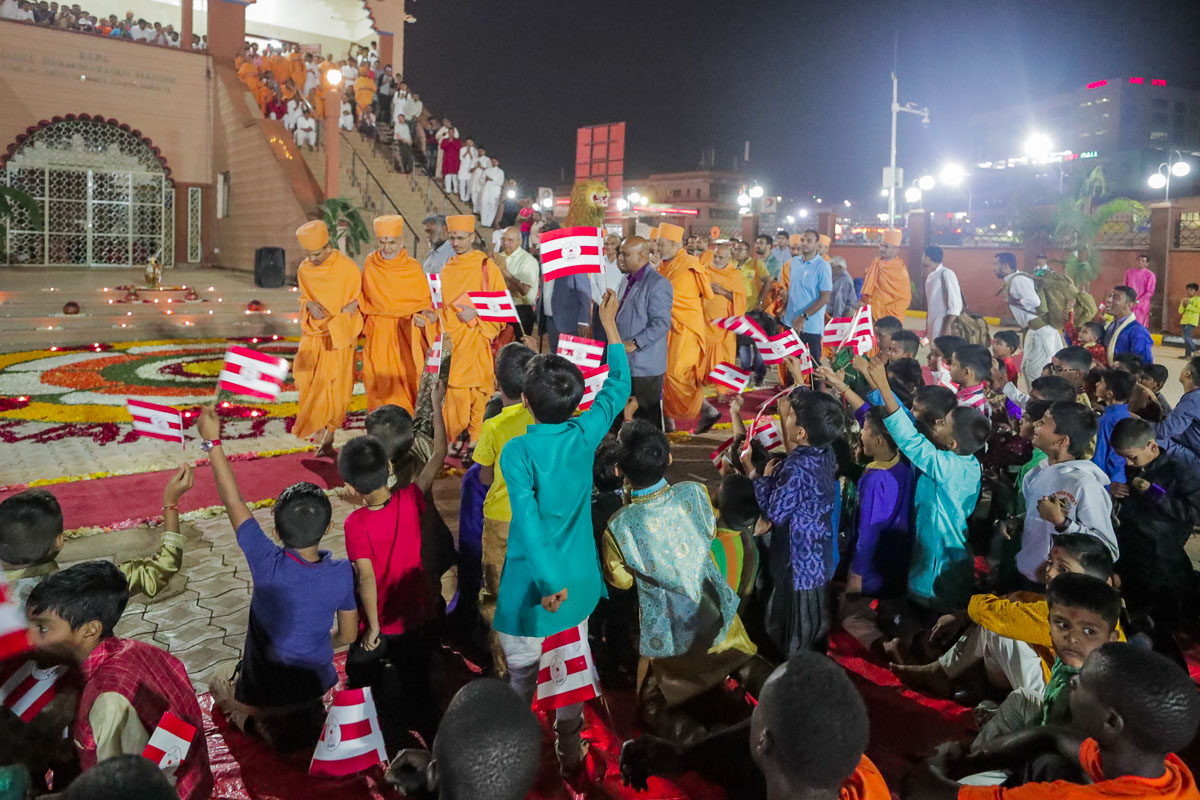 Children welcome Swamishri with BAPS flags