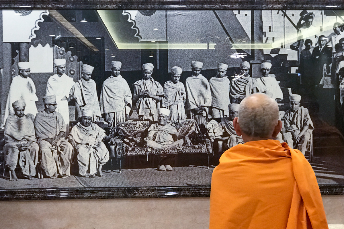 Swamishri observes an old photograph of Yogiji Maharaj and sadhus outside the Kampala mandir in 1970