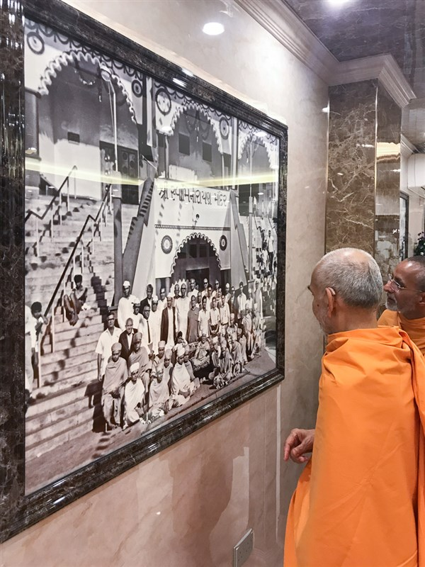 Swamishri observes an old photograph