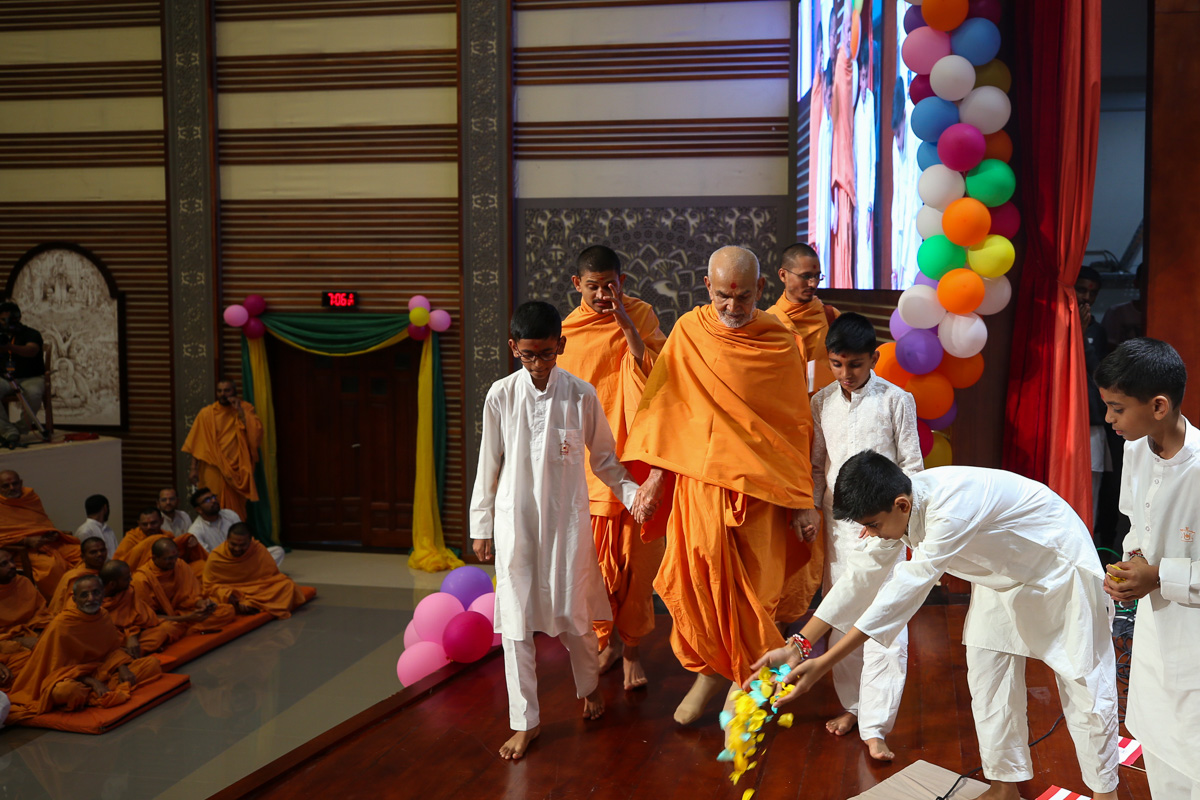 Children welcome Swamishri with flower petals in the evening Bal Din assembly
