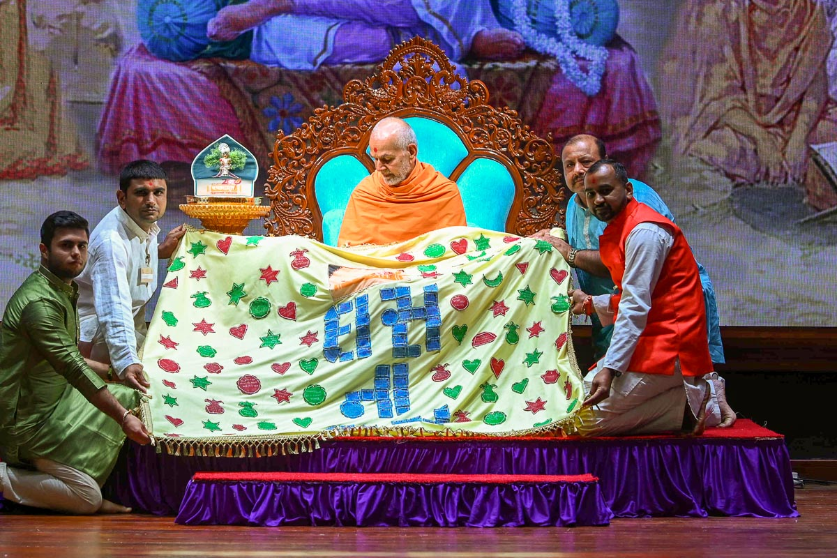 Devotees honor Swamishri with a shawl