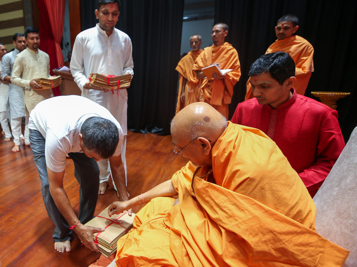 Pujya Tyagvallabh Swami showers flower petals on a Vachanamrut