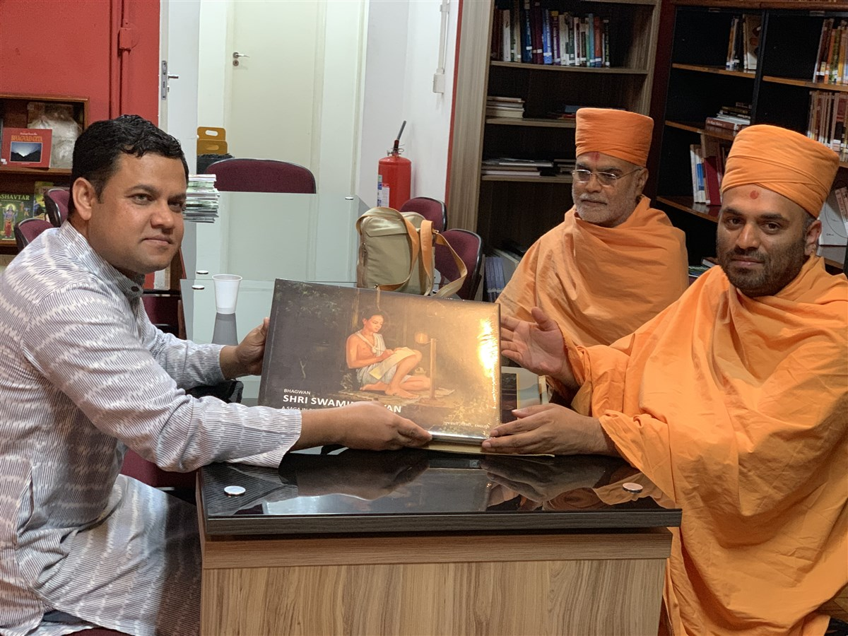 Pujya Priyasevadas Swami presents a book 'Bhagwan Shri Swaminarayan - A Saga in Paintings' to The Hon'ble Mr. Amit Kumar Mishra, Consul General of India in São Paulo, Brazil