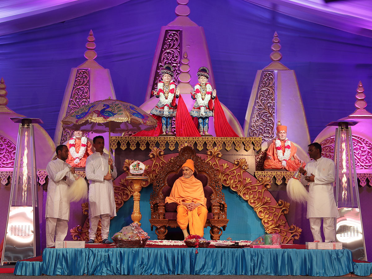 Devotees honor Shri Harikrishna Maharaj with chhatra and chamar