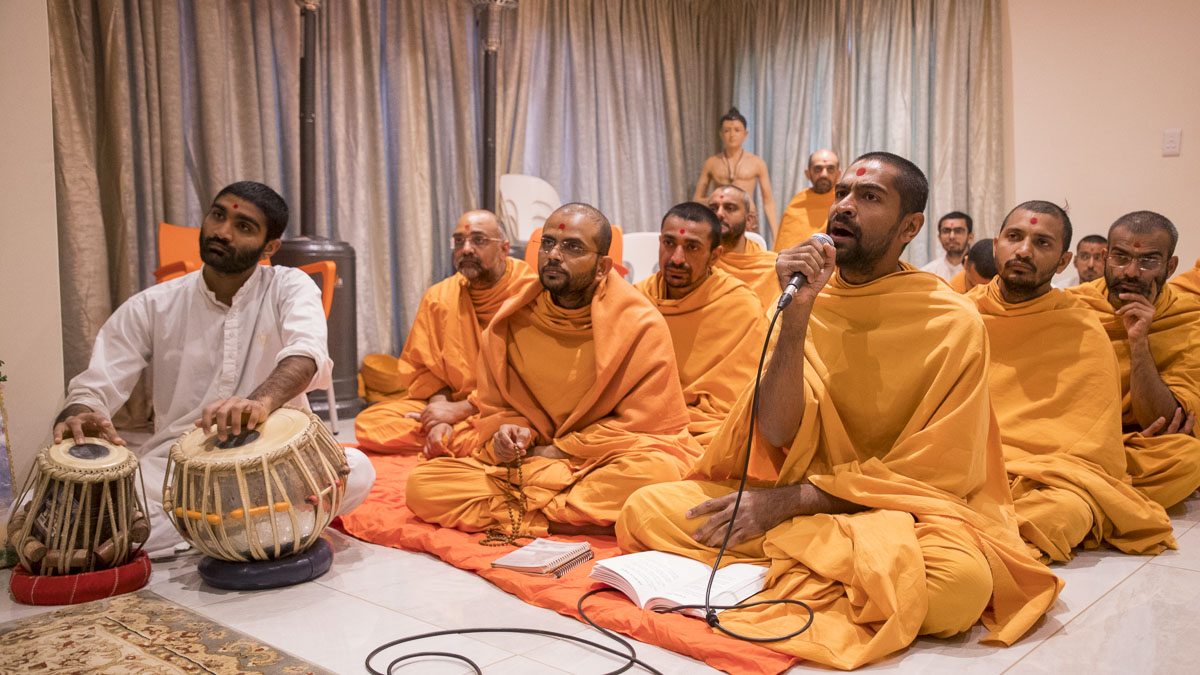 A sadhu sings a kirtan in Swamishri's daily puja