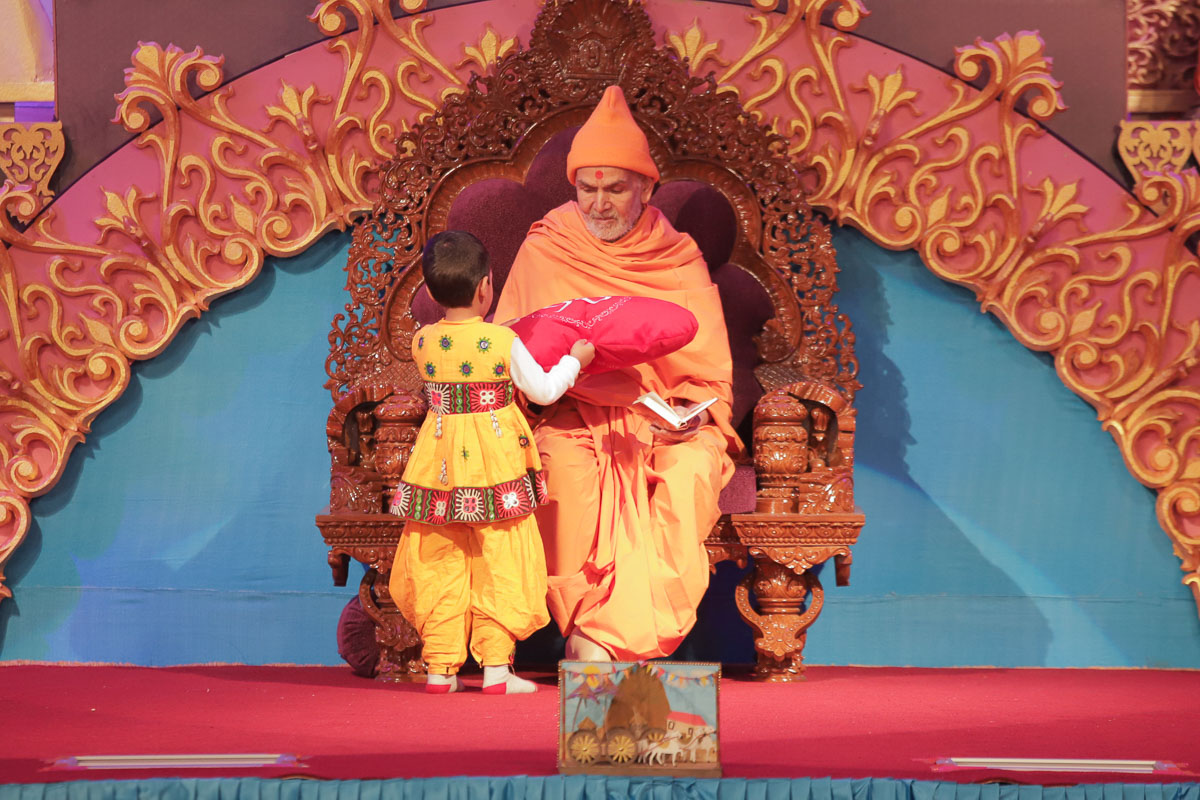 A child presents a pillow to Swamishri