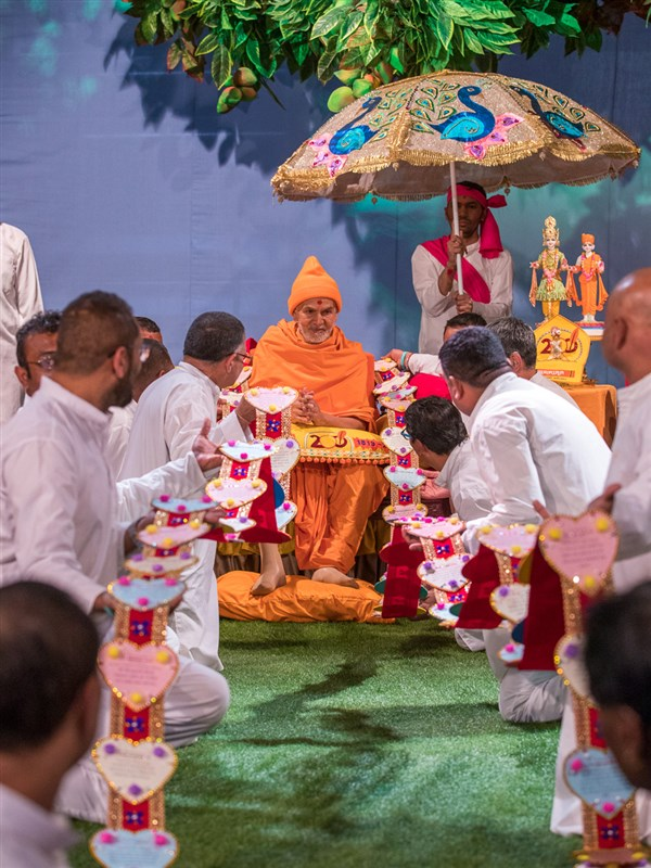 Devotees honor Swamishri with a garland