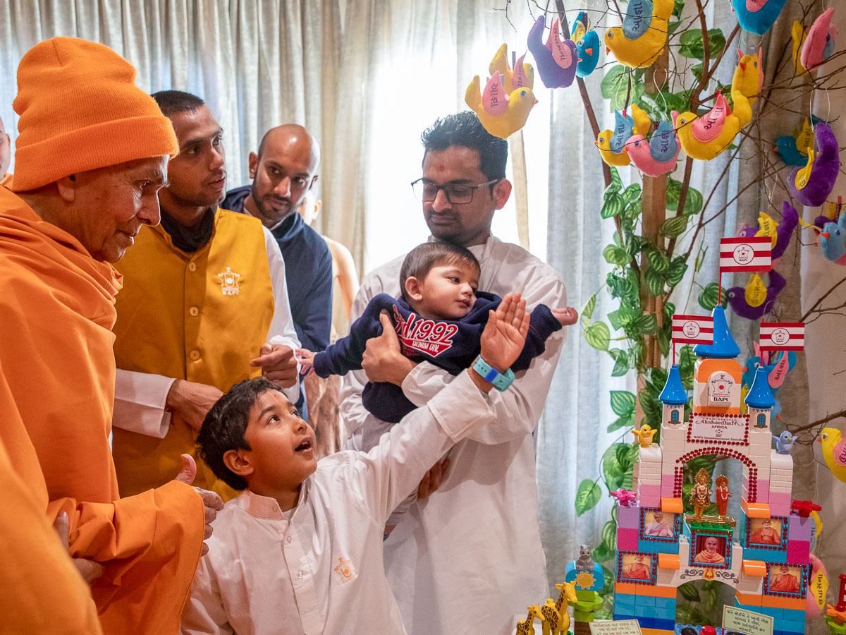 A child explains a display to Swamishri