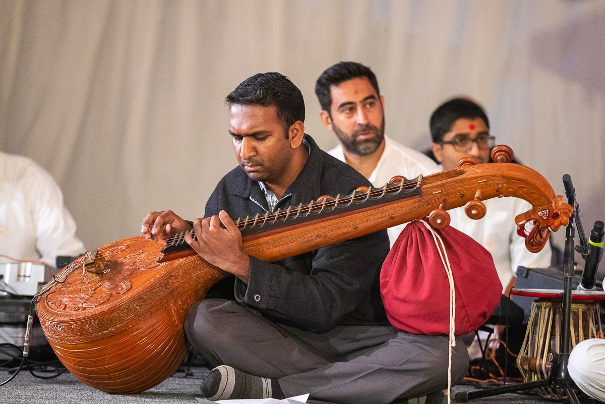 A well-wisher plays veena in Swamishri's daily puja