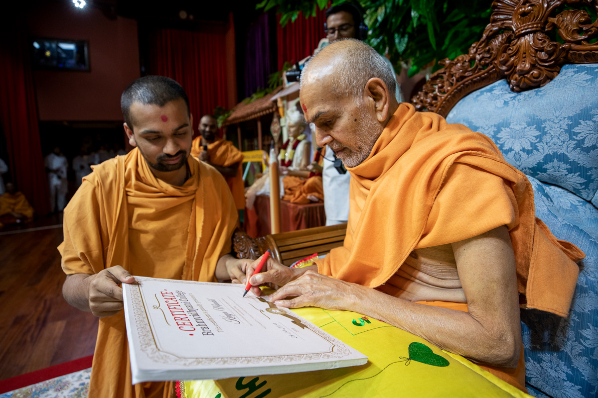 Swamishri signs a certificate