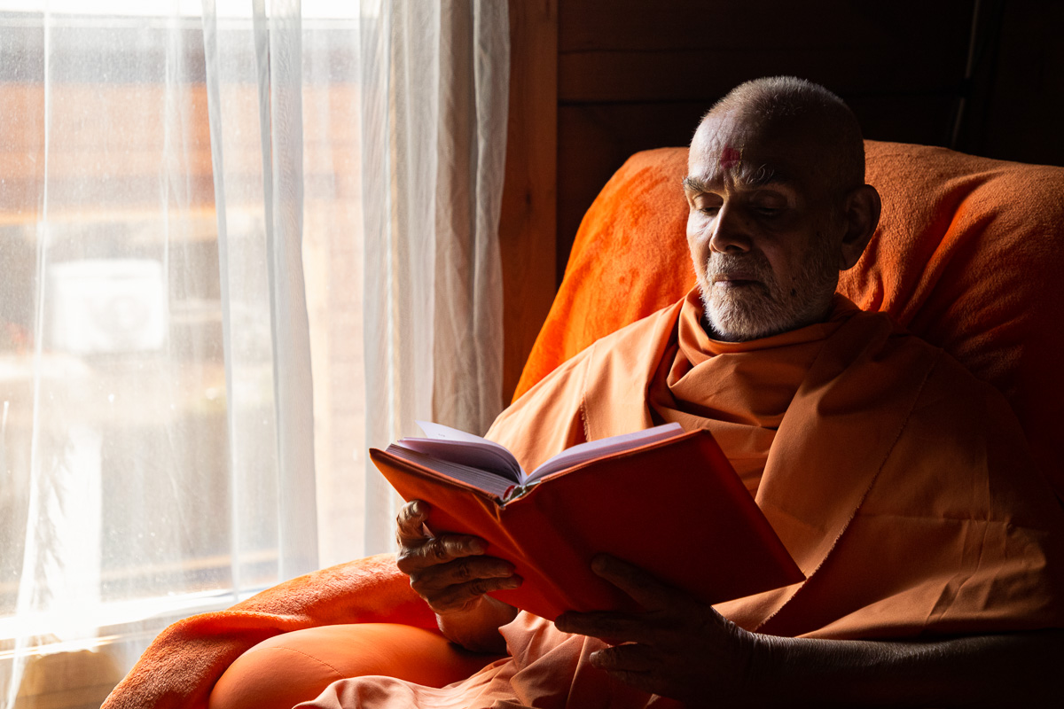 Swamishri reading in his room