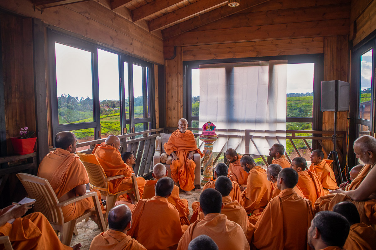 Swamishri and sadhus during a shibir session