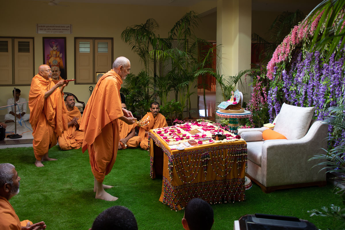 Param Pujya Mahant Swami Maharaj and Pujya Tyagvallabh Swami perform the morning arti at Shanti Van, Nenpur