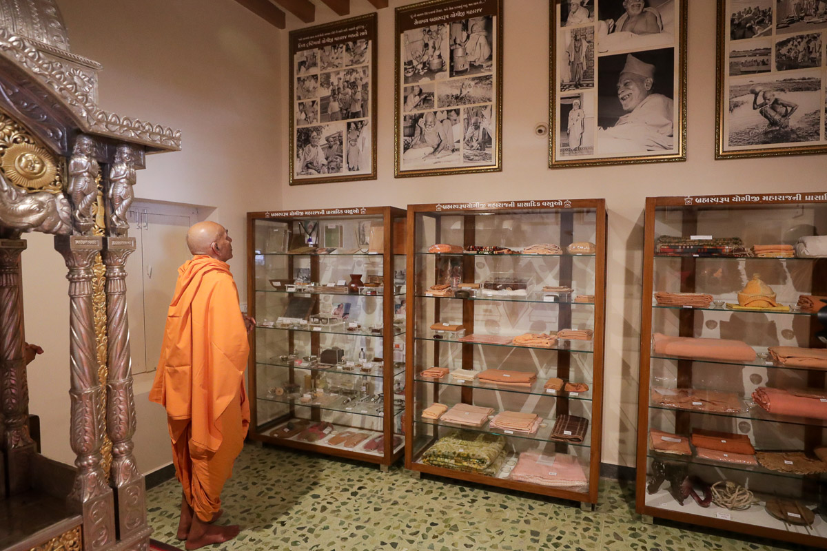 Swamishri observes photos in the room of Brahmaswarup Yogiji Maharaj