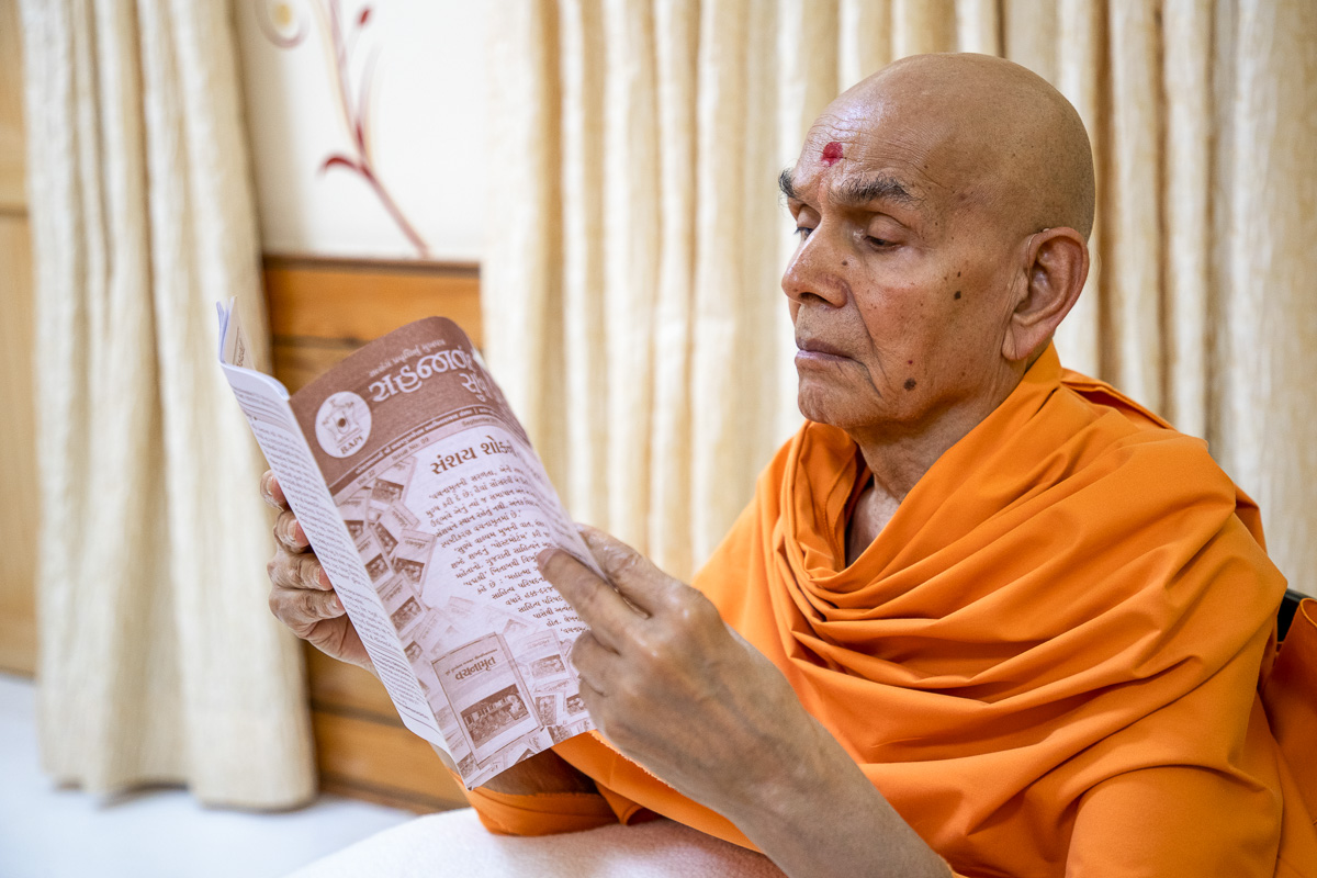 Swamishri reads the monthly magazine for karyakars, 'Sahajanand Sudha'