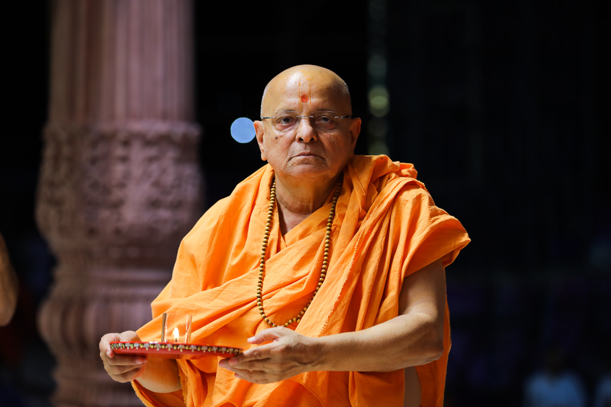 Pujya Ishwarcharan Swami performs arti during the assembly