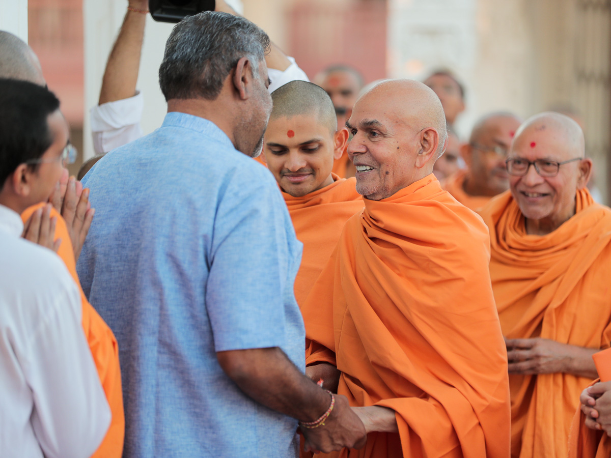 Swamishri shares a light moment with a devotee