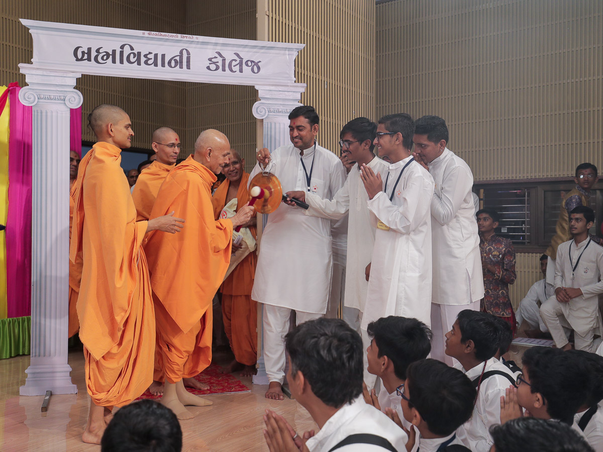 Swamishri strikes a gong on entering the assembly