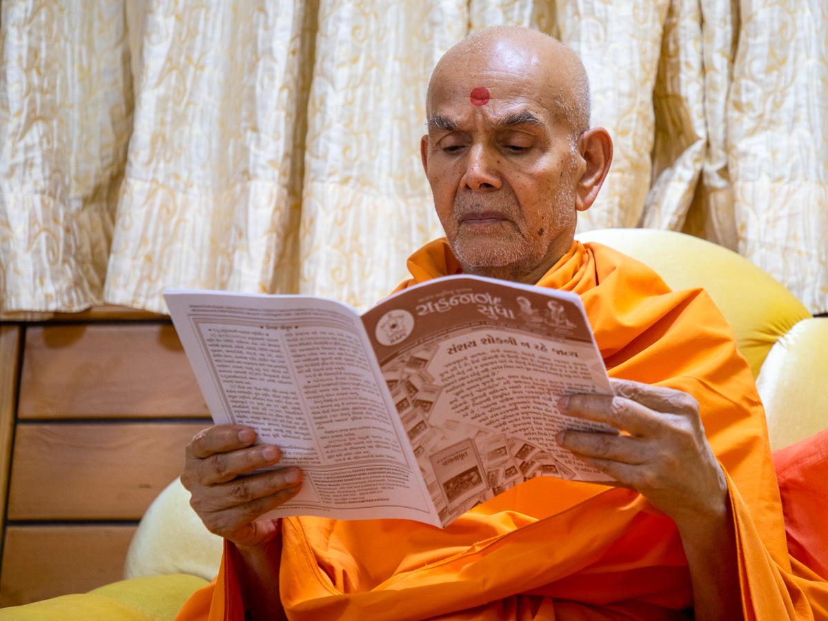Swamishri reads the 'Sahajanand Sudha' newsletter for karyakars