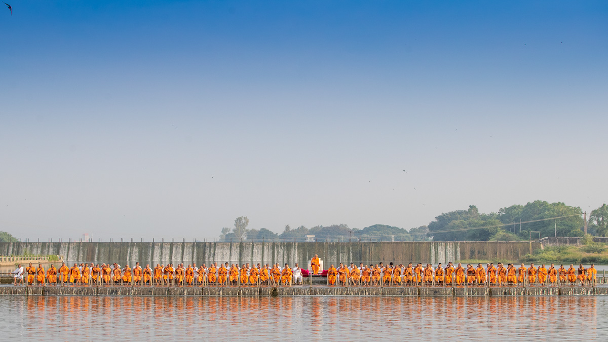 Swamishri, sadhus and devotees pour sanctified water into the River Gondali