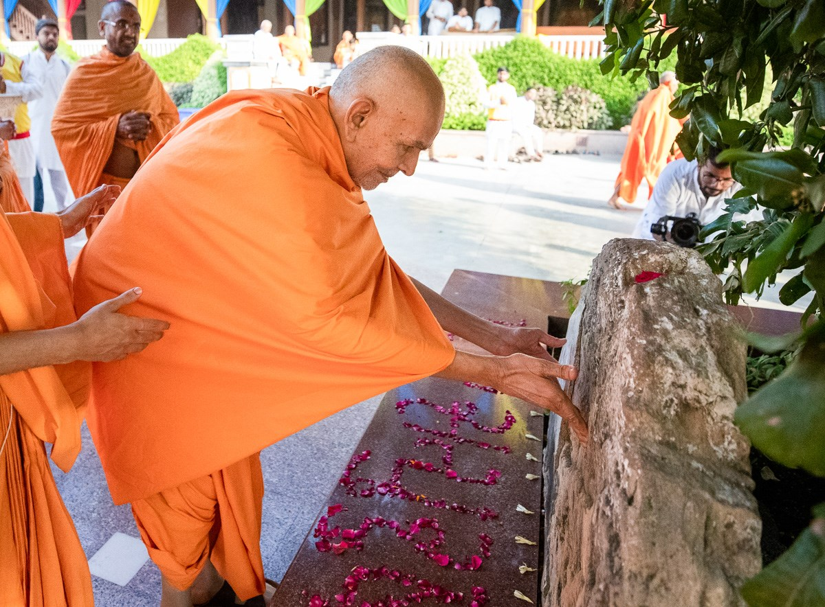 Swamishri engrossed in darshan of a sacred stone sanctified by Aksharbrahman Gunatitanand Swami