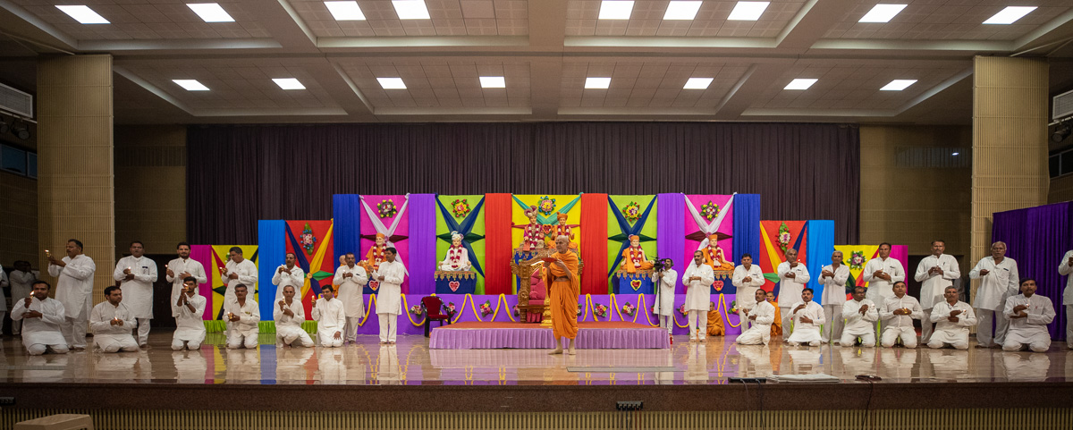 Swamishri and youths perform the evening arti