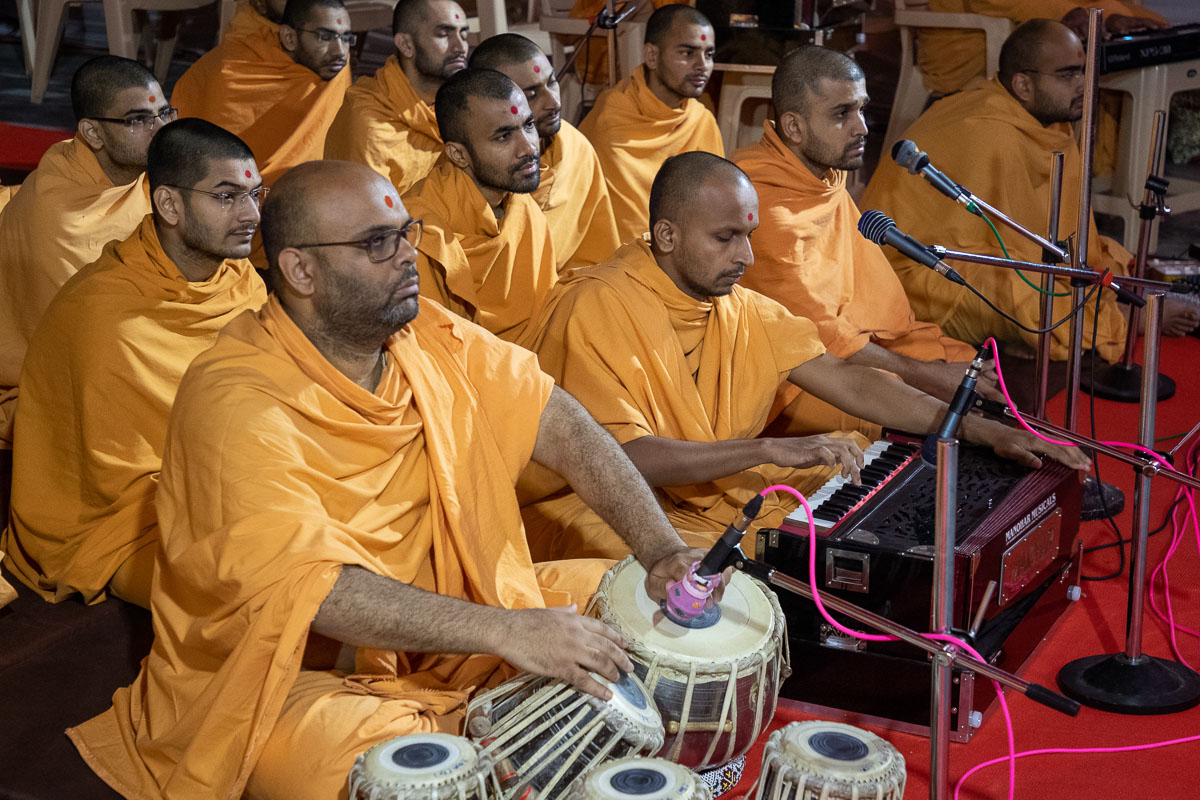 Sadhus sing kirtans in Swamishri's daily puja