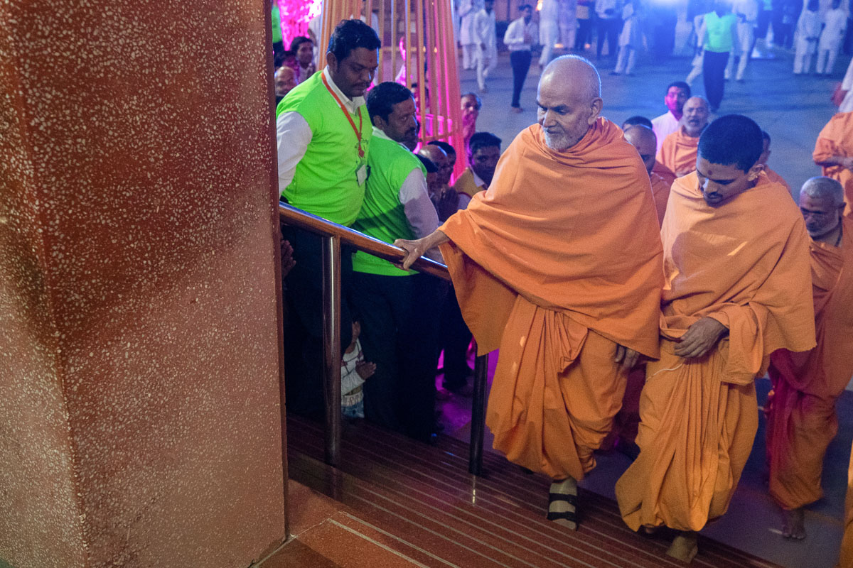 Swamishri climbs the steps of the assembly hall