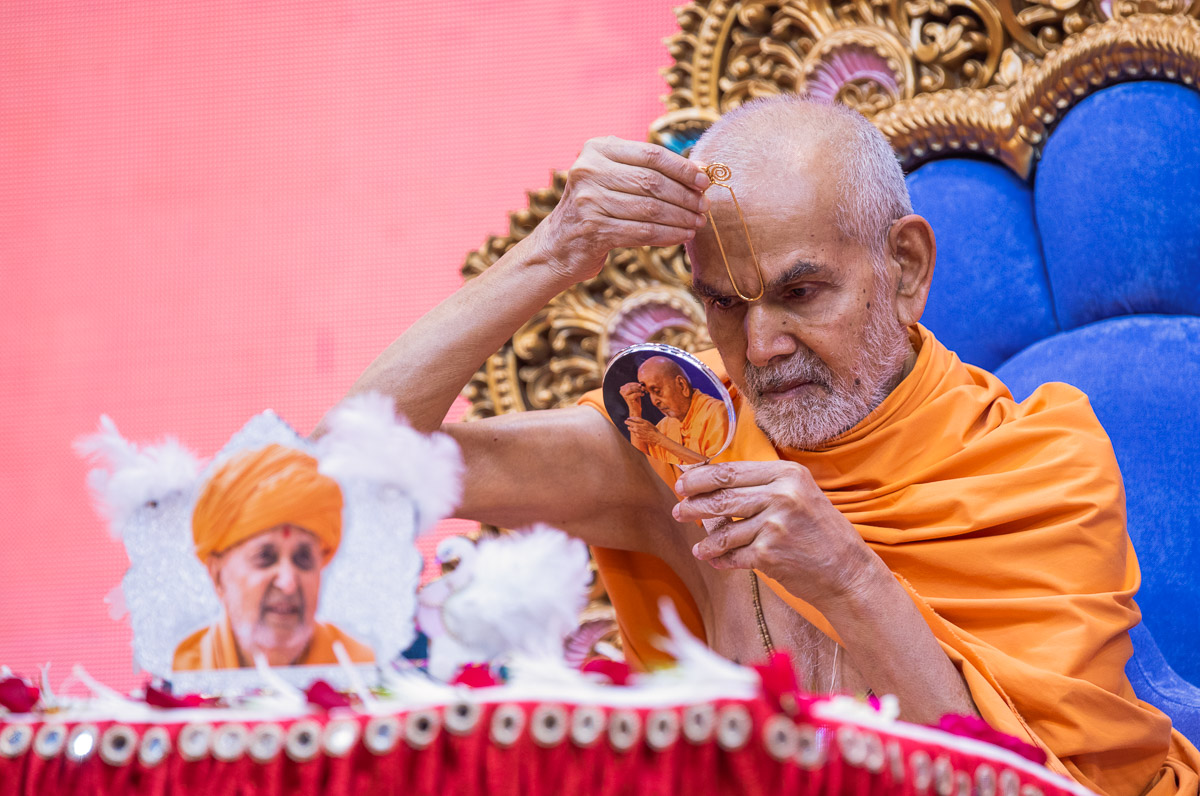 Swamishri applies tilak on his forehead at the beginning of his daily puja